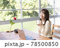窓辺でパソコンの前の席に座りコーヒーを飲む20代女性 78500850