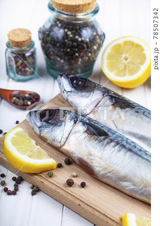 Raw mackerel on a cutting board with spices. 78507342