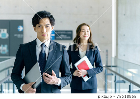 オフィスを移動するスマホを持ったスーツの若いビジネスマン 78518968