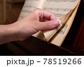 Pianist's hand turns sheet music page. Close-up. 78519266