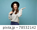 Photo of attractive brunette happy joyful young woman pointing hand at free space for text wearing 78532142