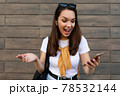Photo of attractive shocked surprised young woman wearing casual clothes standing in the street 78532144