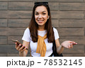 Photo of attractive smiling young woman wearing casual clothes standing in the street holding mobile 78532145