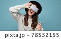 panoramic Closeup of attractive young happy woman wearing black hat and grey sweater holding phone 78532155