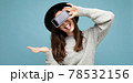 beautiful young woman wearing black hat and grey sweater holding phone showing smartphone showing 78532156