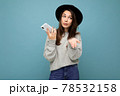 young asking dissatisfied brunette woman wearing black hat and grey sweater holding smartphone 78532158