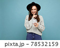 Attractive young smiling woman wearing black hat and grey sweater holding smartphone looking down 78532159