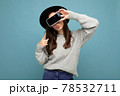 beautiful young woman wearing black hat and grey sweater holding phone showing smartphone by 78532711