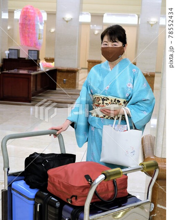 ホテルロビーでチェックインするマスク姿の和服の女性 78552434