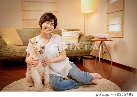 リビングで愛犬とリラックスする若い女性 78555498