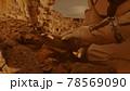 Unrecognizable cosmonaut examining soil on Mars 78569090