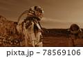 Male astronaut adjusting camera on colleague 78569106