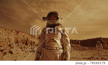 Female astronaut admiring terrain of Mars 78569179