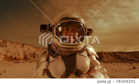 Female astronaut looking at camera on Mars 78569205