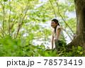 木の幹に座る少女 78573419