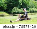 芝生で寛ぐ男性とドーベルマン 78573420