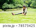 芝生でストレッチをする少女 78573425