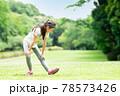 芝生でストレッチをする少女 78573426