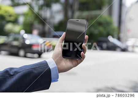 スマートフォンを持った若い男性の手元 78603296
