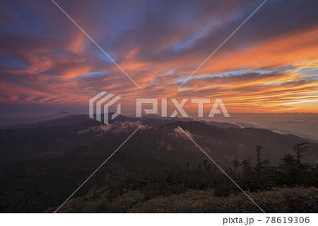 志賀高原から見渡す山々の上空の雲が並ぶような形になって不思議な色に焼けだした 78619306