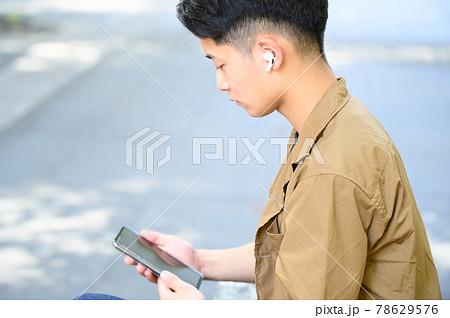 音楽を聴く男性 ワイヤレスイヤホン 78629576