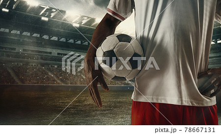 Cropped male soccer, football player standing with ball at the stadium during sport match on light sky background with flashlights. 78667131