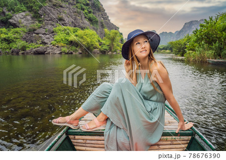 Woman tourist in Trang An Scenic Landscape Complex in Ninh Binh Province, Vietnam A UNESCO World Heritage Site. Resumption of tourism in Vietnam after quarantine Coronovirus COVID 19 78676390