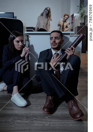 Two horrified office managers sitting on the floor by desk 78676969