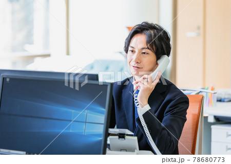 電話を受けながらパソコンを使うビジネスマン 78680773