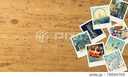アンティークな木のテーブルの上に並べられたポラロイド写真。真上からのアングル 78694760