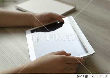 机の上でタブレット端末を持っている子供の手 78695084