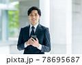 オフィスでスマホを持ったスーツ姿のビジネスマン 78695687