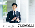 オフィスでスマホを持ったスーツ姿のビジネスマン 78695688
