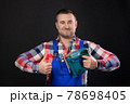 Caucasian male repairman in glasses with woodworking tools in hand shows thumb up. Portrait of a carpenter on a black studio background. Approval concept 78698405