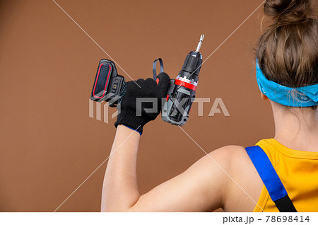 Back view energetic strong young Caucasian woman in a work uniform and goggles shows that she is strong with a screwdriver in her hand 78698414
