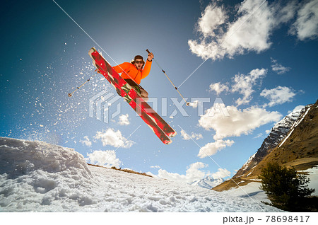Fly young caucasian man jumping from a springboard on skis 78698417