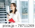 オフィスでスマホを操作するビジネスカジュアルのビジネスウーマン 78711269