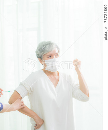 Senior asian woman receiving the injection of the coronavirus vaccine by a nurse to receive the antibodies, immunize the population. 78722800