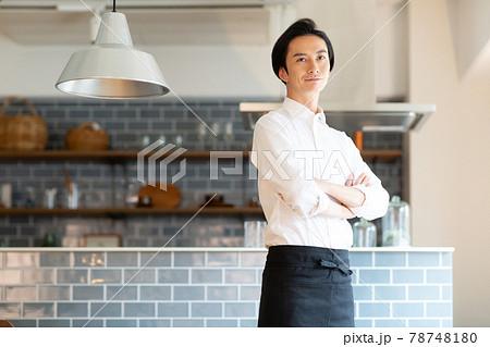 エプロンをしてキッチンに立つ男性 78748180