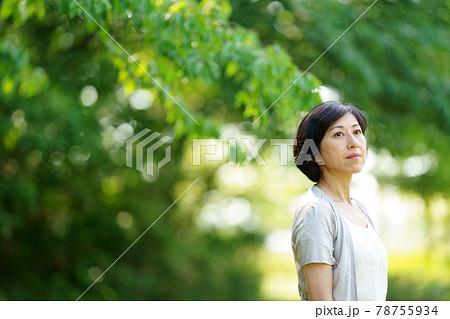 緑の中で遠くを見る中年女性 緑の中に立つミドル女性 78755934