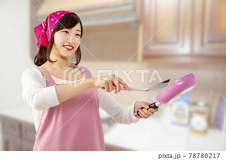 キッチンでフライパンで料理を作る笑顔の若い女性1人 78780217
