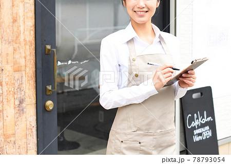 飲食店で働くエプロン姿の女性が店頭で伝票を持つイメージ 78793054