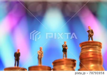 積まれたコインと順に並んだ4人のミニチュアのビジネスマン_クローズアップ 78793958
