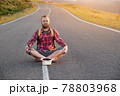 Positive bearded caucasian male tramp barefoot sitting on a country road at sunset with a passing charity donation hat 78803968