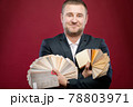 Handsome caucasian joyful furniture businessman standing in studio on red background holding two fans of furniture coating sample testers, smiling, looking at camera. Studio portrait 78803971