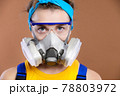 Portrait of a young Caucasian woman in protective equipment for the organs of vision and respiration. Look into the camera. A girl in a respirator and goggles in working overalls. 78803972