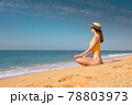 Meditation by the sea on a sunny day. Young caucasian woman in a yellow swimsuit sits on the golden sand in a lotus position in a straw hat and sunglasses with a rosary in her hand 78803973