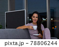 Woman enjoying a cup of tea in the night sitting on a couch in the living room 78806244