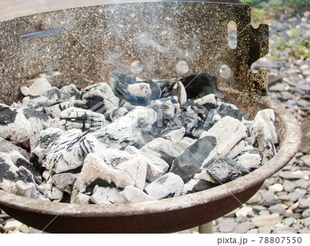 バーベキューセットで火が付いて煙を上げる炭 78807550