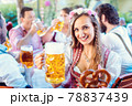 Woman toasting to the camera with glass of beer in Bavarian pub 78837439